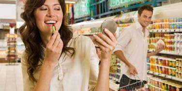 girl putting on makeup at grocery store