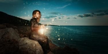 witchy looking woman sits on a rock. at sunset, looking at ocean