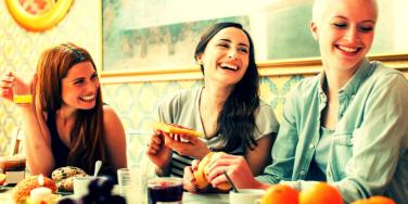 three women eating together and laughing