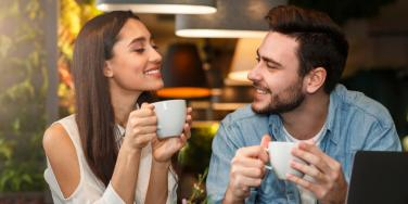 man and woman smiling at each other over coffee