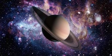 planet saturn in front of galaxy