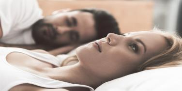 worried woman laying in bed next to man