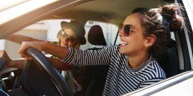 women driving in car smiling sunglasses