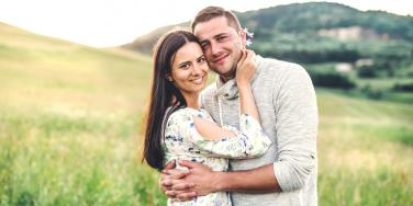 happy and loving couple in a good marriage posing on a field