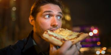guy eating pizza being told a woman isn't interested after a first date