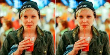 woman in a beanie drinking a smoothie