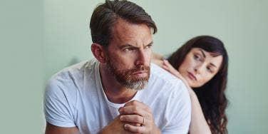 man sitting sternly woman behind him