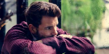 man looking out a window giving silent treatment