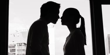 black and white silhouette of man and woman in front of a window