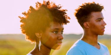 Black couple in their late twenties looks at the horizon, backlit by sun