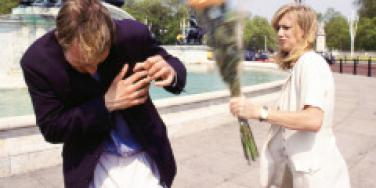 woman hitting man with bouquet of flowers
