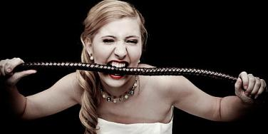woman biting down on whip