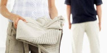 Woman folding a sweater into luggage