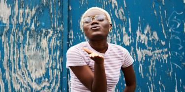 Black woman with short blonde hair blowing a kiss