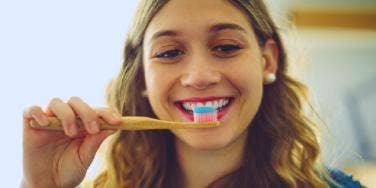 woman brushing her teeth smiling