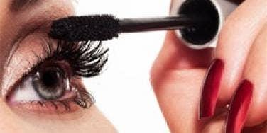 woman wearing lots of makeup putting on mascara