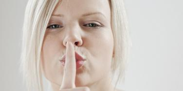 Woman with fingers on lips