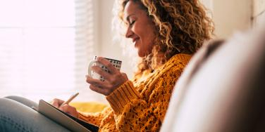 woman writing on the couch while holding a mug