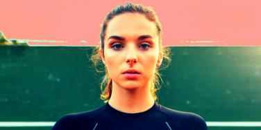 woman staring forward pink and green background