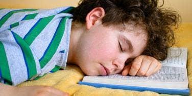 boy sleeping on book