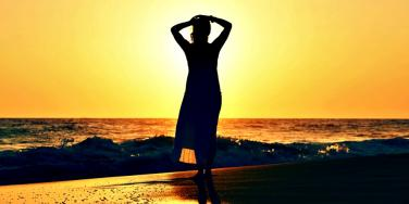woman standing on the beach alone.