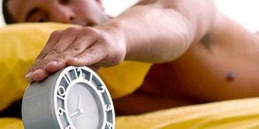 man touching alarm clock
