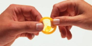 woman holding yellow condom