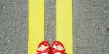 woman wearing red shoes standing on yellow road lines
