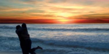 Couple hugging joyfully at sunrise on the beach