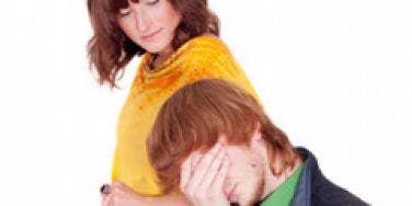 A man hides his eyes as a woman passes.