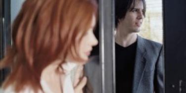 Woman closing the door on a man
