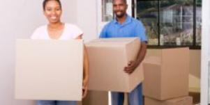 Couple holding moving boxes