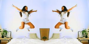 woman in the air jumping on bed