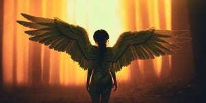woman wearing angel wings in shadows