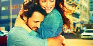 caucasian couple hugs, man serious, woman smiling