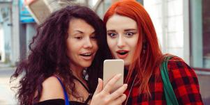 Two young women looking at a phone in shock