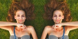 woman with striped shirt laying in grass smiling
