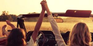 two women holding hands on road trip