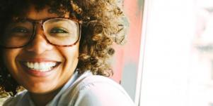 woman with glasses and curly hair smiling