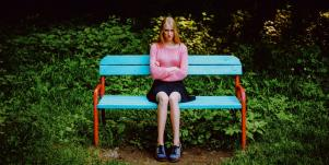 angry woman sitting on a bench with arms crossed