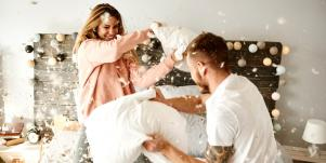 man and woman having a pillow fight