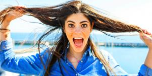 woman holding her hair with tongue out looking happy