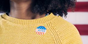 young Black woman wearing an I voted sticker