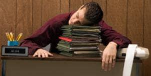 man asleep at his desk at work