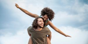 woman getting piggyback ride flying like airplane