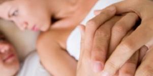 couple in bed with hands clasped