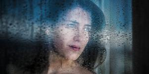 woman looking out a window at the rain