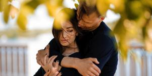 couple hugging in fall leaves