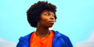 woman in blue jacket staring off blue background
