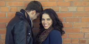 man and woman standing by a brick wall